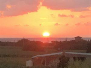 水平線の少し上に沈む夕日